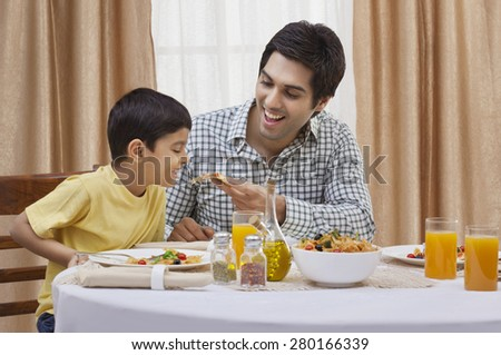 Happy father feeding piece of pizza to his son at restaurant - stock photo
