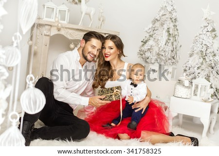 Happy father giving a Christmas present to his wife. Happy Family in Christmas Time - stock photo