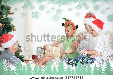 Happy father giving a present to his daughter sitting on the sofa against snowflakes and fir trees in green - stock photo