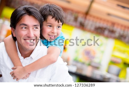 Happy father giving his song a piggyback ride and smiling - stock photo