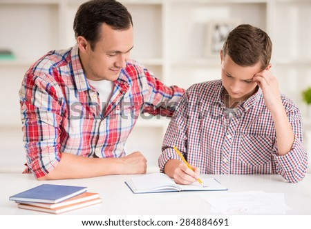 Happy father helping his son to do homework. - stock photo