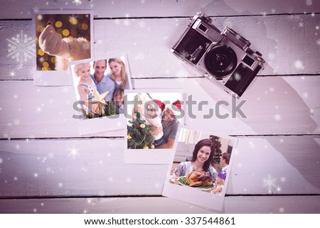 Happy father helping his son to put an angel on the Christmas tree against instant photos on wooden floor - stock photo