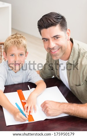 Happy father helping son with homework at table at home in kitchen - stock photo