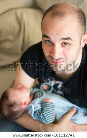 Happy father holding his few days old son