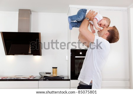 Happy father holding his young child up - stock photo