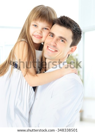 Happy father holding smiling daughter in his arms - stock photo