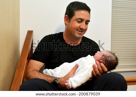 Happy father holds his newborn baby few minutes after childbirth. - stock photo