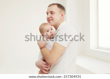 Happy father hugging his baby at home in white room - stock photo
