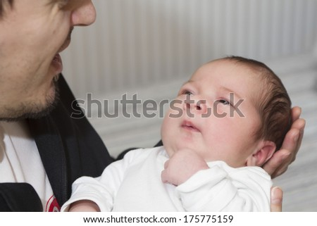 Happy father is holding his newborn baby