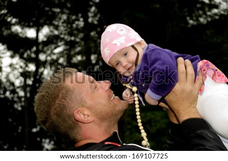 Happy father is lifting up his smiling baby  - stock photo