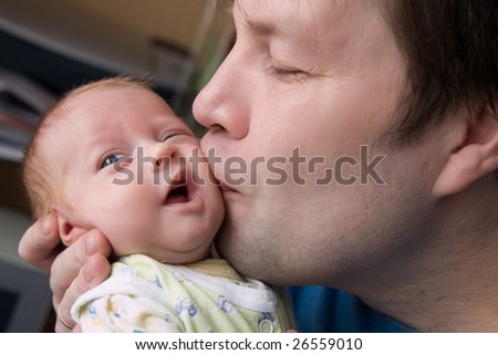 Happy father kisses his small daughter with love