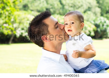 happy father kissing baby outdoors