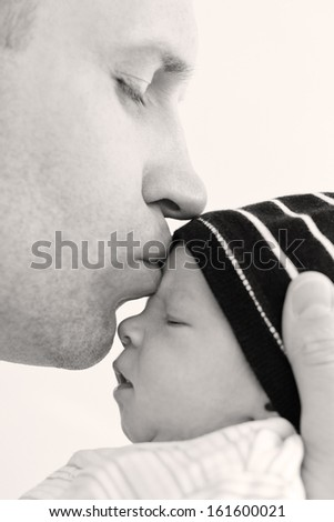 happy father kissing baby son on a white background - stock photo