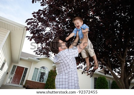 Happy father lifting his cute son in the air - stock photo