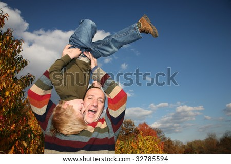 Happy father lifting son upside down over blue sky - stock photo