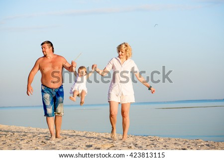 Happy father, mother and little daughter playing on the beach in summer