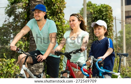 Happy father, mother and son walking outdoors with bicycles