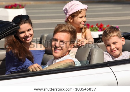 Happy father, mother and two children ride in convertible car; focus on man - stock photo