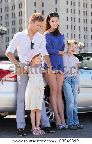 Happy father, mother and two children stand near convertible car - stock photo