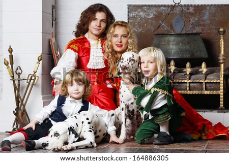 Happy father, mother and two sons in medieval costumes sit with two dalmatians near fireplace. - stock photo