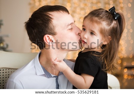 happy father on hands small to the daughter, strong embraces and kisses. Bright festive fires on a background. Waiting for a holiday. Christmas.