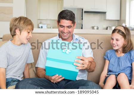 Happy father opening gift given by children on sofa at home - stock photo