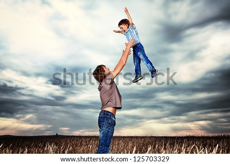 Happy father playing with his little son in the wheat field over beautiful cloudy sky. - stock photo