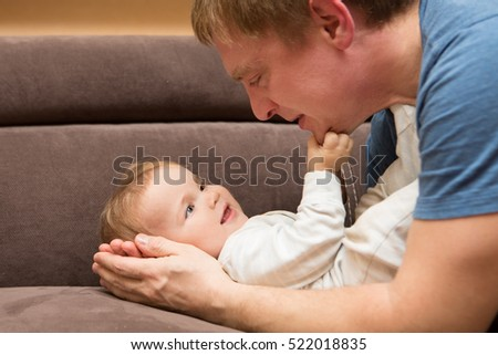 Happy father plays with his baby at home