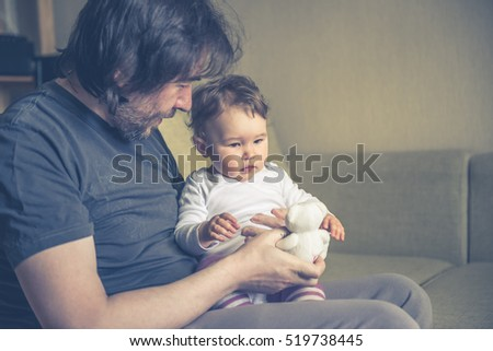 Happy father plays with his baby on the couch at home. The one-year child looks at the teddy bear.