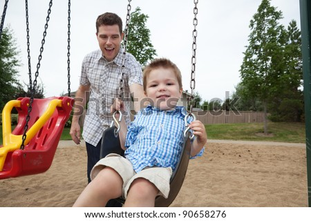Happy father pushing boy on swing in playground - stock photo