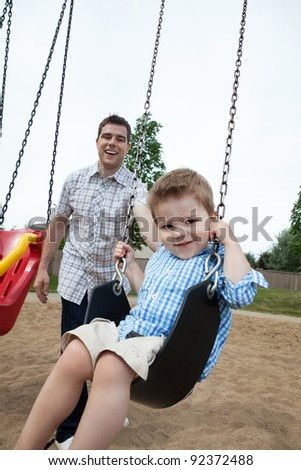 Happy father pushing his son on a swing - stock photo
