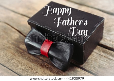 Happy father's day concept. Black and red leather bow tie and gift box on wooden table, close up - stock photo