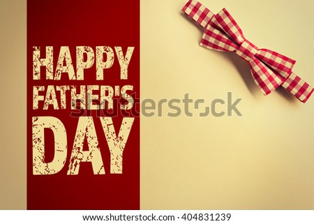 Happy Father's Day. Red cell bow tie on beige background - stock photo