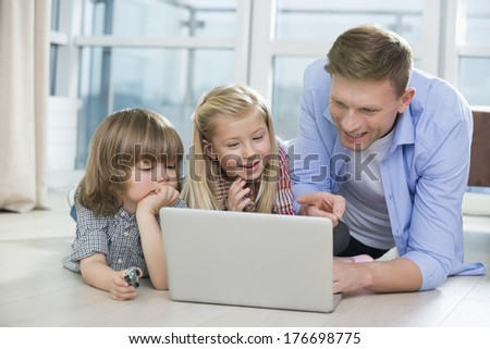 Happy father showing something to children on laptop at home