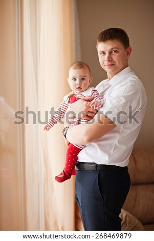 Happy Father sitting with baby in her arms - stock photo