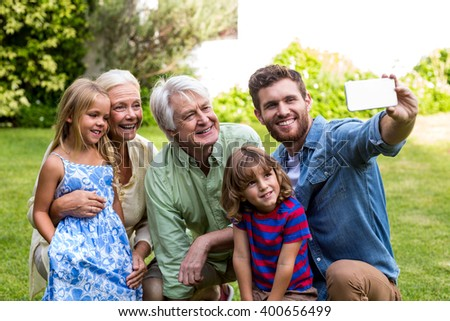 Happy father taking selfie with family while sitting in yard - stock photo