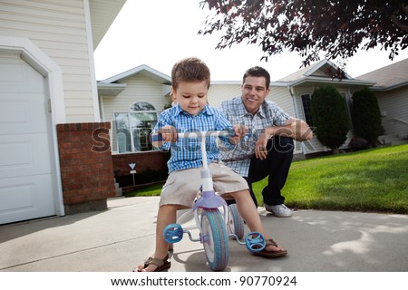 Happy father teaching his adorable son to ride a tricycle - stock photo