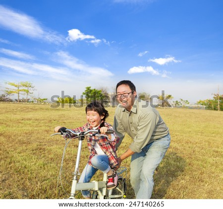 happy Father teaching little girl to ride bicycle - stock photo