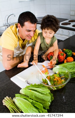happy father teaching toddler son how to make salad in modern kitchen - stock photo