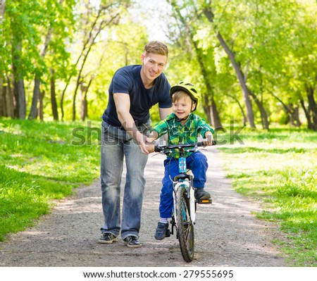Happy father teaching young son to ride a bike - stock photo