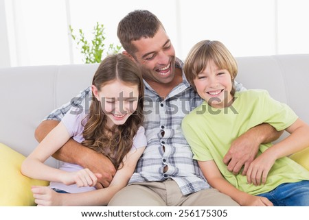 Happy father tickling children while sitting on sofa at home - stock photo