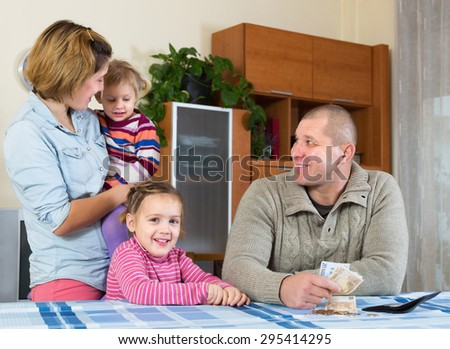 Happy father with banknotes sitting at table, cheerful family staying nearby. Focus on man - stock photo