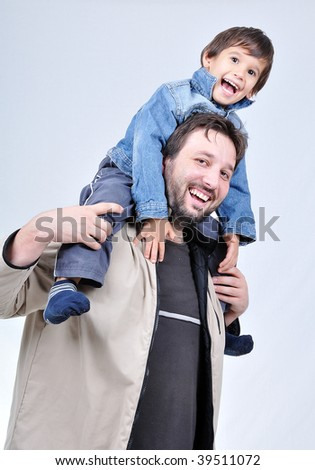Happy father with boy on his shoulders - stock photo