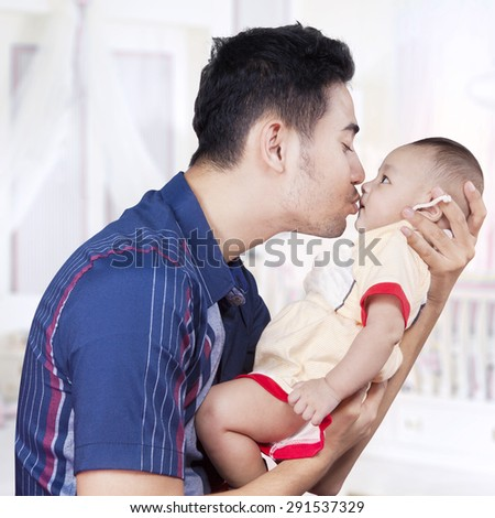 Happy father with casual clothes, holding and kiss his three months baby in the bedroom - stock photo