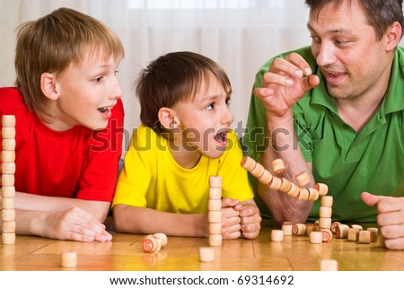happy father with children playing on the floor - stock photo