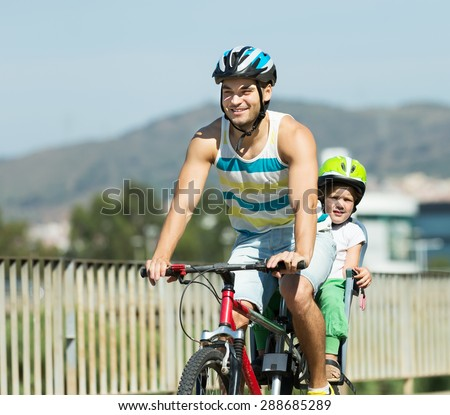 Happy father with daughter in helmets cycling though street