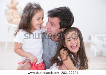 Happy father with daughters spending quality time together at home - stock photo