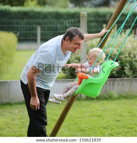 Happy father with his adorable baby daughter playing with swing in the garden at backyard of the house