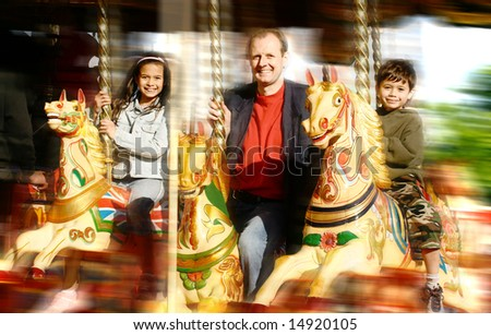 Happy father with his daughter and son enjoying the carousel ride at the steam fair - stock photo