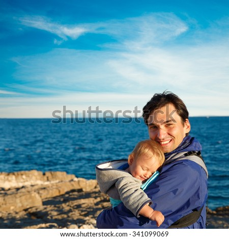 Happy Father with His Little Son in Carrier on Sea Background. Family Recreation Concept. Square Photo with Copy Space. - stock photo